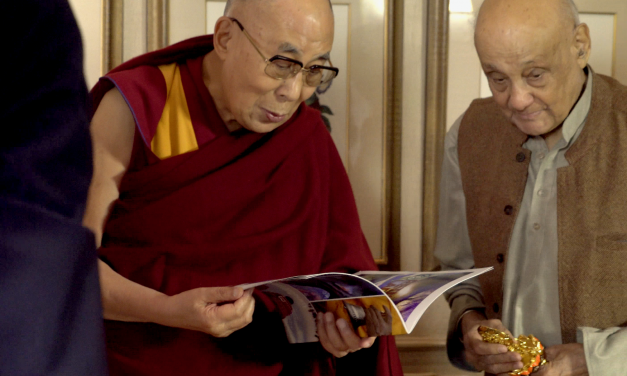 The Dalai Lama reading the Red Rock Entertainment brochure.